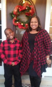 Chenita and son wearing coordinating red and black flannel shirts stand in front of a Christmas wreath